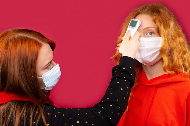 Duas meninas com máscaras médicas medem a temperatura corporal com um termômetro sem contato. foto em uma parede vermelha. conceito de vírus e pandemia.