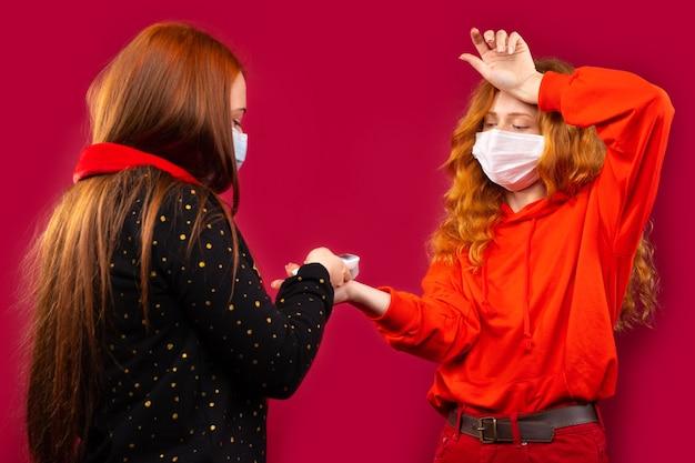 Duas meninas com máscaras médicas medem a temperatura corporal com um termômetro sem contato. foto em uma parede vermelha.