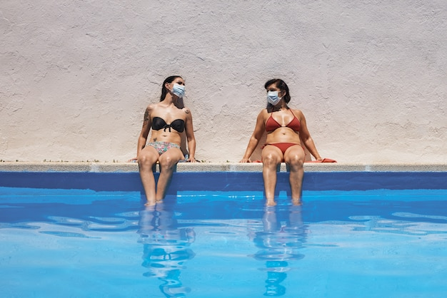 Duas meninas com máscaras sentadas na piscina tomando sol