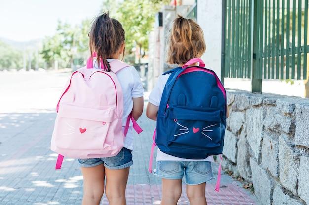 Duas meninas com mochilas na rua