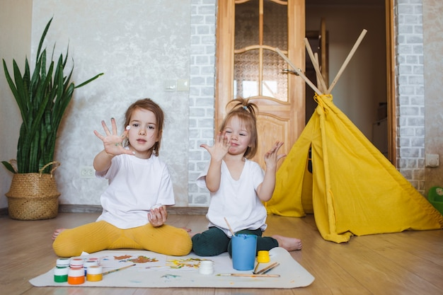 Duas meninas com roupas de cores claras sentam-se no chão de joelhos e desenham com entusiasmo aquarelas brilhantes.