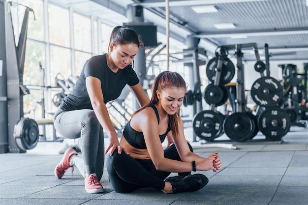 Duas meninas com roupas esportivas estão juntas no ginásio durante o dia.