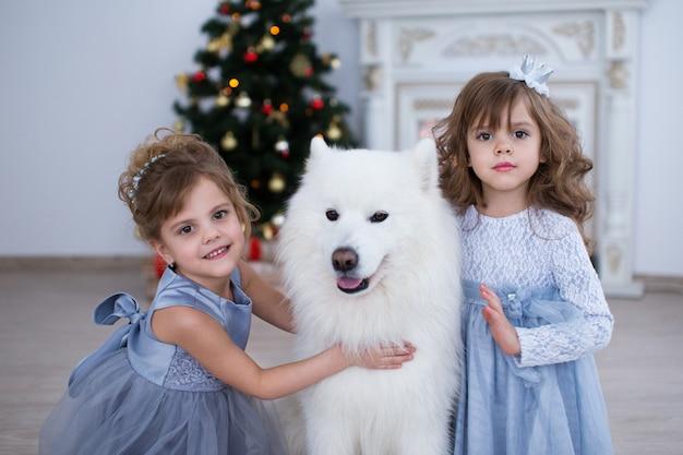 Duas meninas com um cachorro e uma árvore de natal