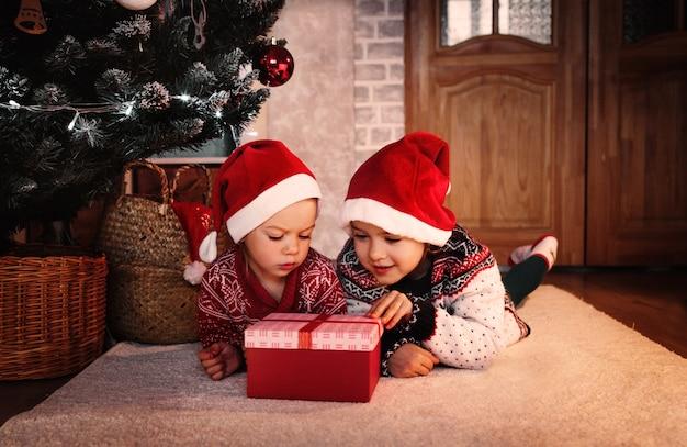 Duas meninas com um chapéu de papai noel abrem uma caixa de presente de natal debaixo da árvore
