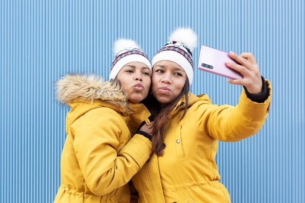 Duas meninas com um gesto sexy e as mesmas roupas tirando uma foto delas com um smartphone ao ar livre.