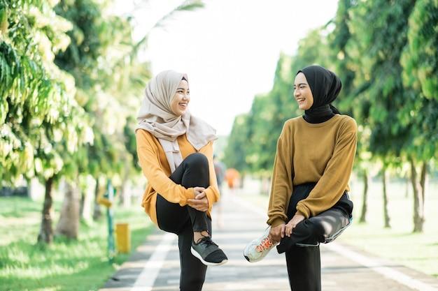 Duas meninas com véu alongando os músculos das pernas levantando e segurando a perna dobrada com os braços antes de correr no parque