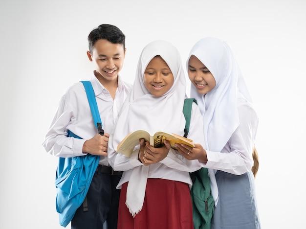 Duas meninas com véu e um menino com uniformes do ensino médio sorrindo ao ler um livro juntos enquanto carregam ...