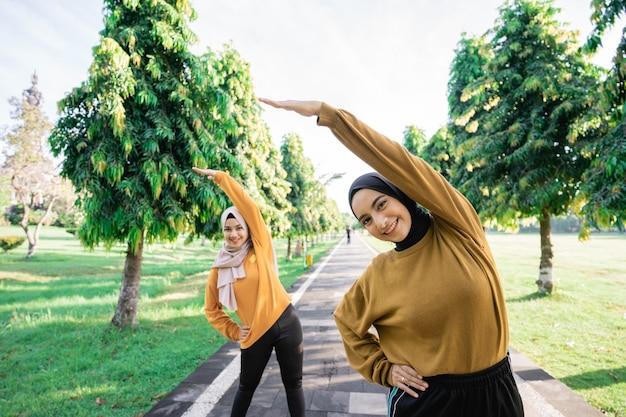 Duas meninas com véu fazem alongamentos de braço, levantando os braços para cima com o corpo inclinado para o lado antes de se exercitar no parque