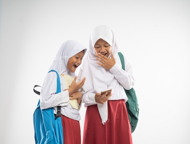 Duas meninas com véu vestindo uniformes do ensino fundamental usando um telefone celular junto com expressões chocadas ...