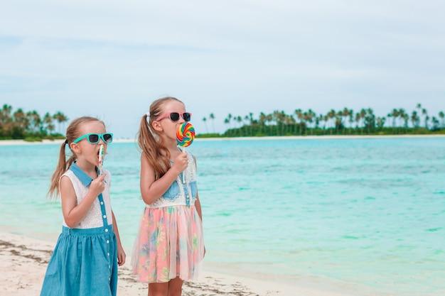 Duas meninas comendo pirulitos brilhantes na praia