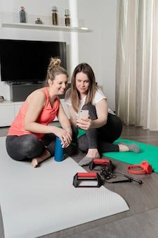 Duas meninas conversando na chamada de vídeo depois de praticar esportes em casa.