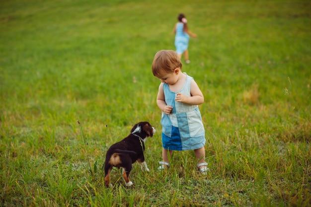 Duas meninas correm com um cachorrinho no campo