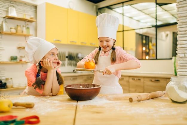 Duas meninas cozinhando em bonés esfregando laranja na tigela