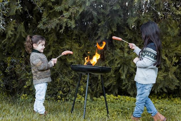 Duas meninas cozinhar salsichas no churrasco ao ar livre