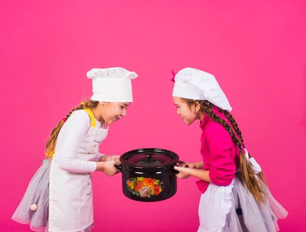 Duas meninas cozinheiros carregando panela pesada