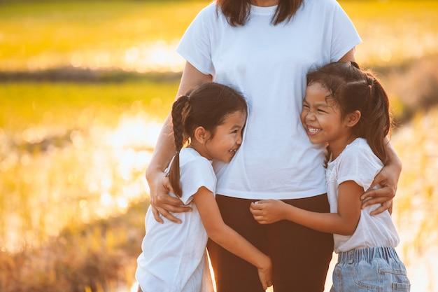 Duas meninas criança asiática, abraçando sua mãe e se divertindo para brincar com a mãe no arrozal