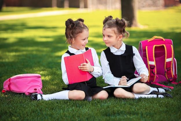 Duas meninas da escola com mochila rosa sentada na grama depois das aulas e ler livro ou estudar lições,
