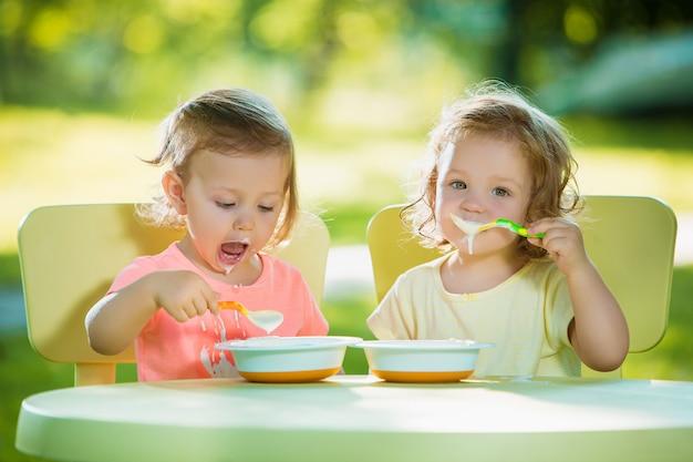 Duas meninas de 2 anos de idade, sentado em uma mesa e comendo juntos contra um gramado verde