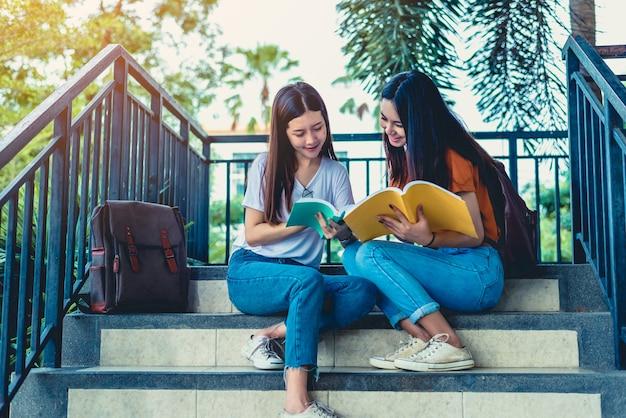 Duas meninas de beleza asiáticas lendo e tutoria livros para exame final juntos