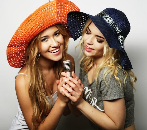 Duas meninas de beleza com um microfone
