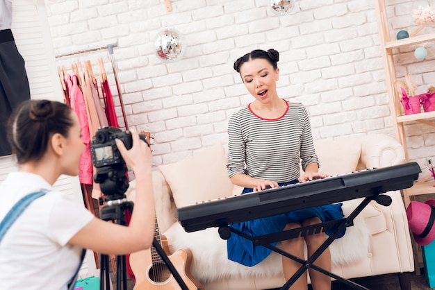 Duas meninas de blogueiro de moda jogar teclado.