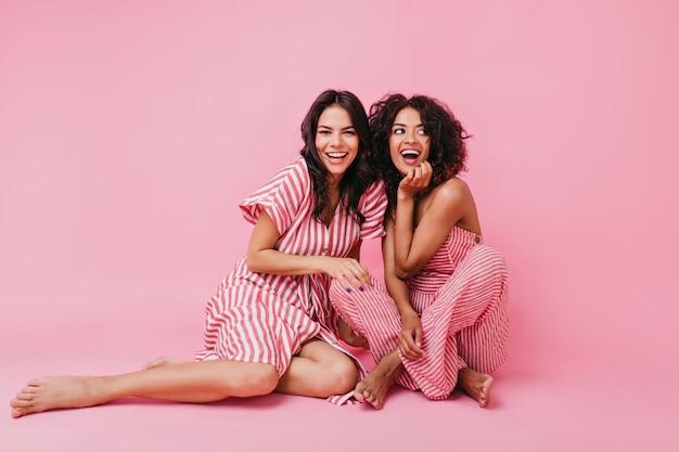 Duas meninas de cabelos escuros, uma com lisos e outra com cacheados, vestidas de pijama macio e lindo, se divertindo e brincando