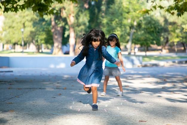 Duas meninas de cabelos negros animadas jogando amarelinha no parque da cidade. comprimento total, copie o espaço. conceito de infância