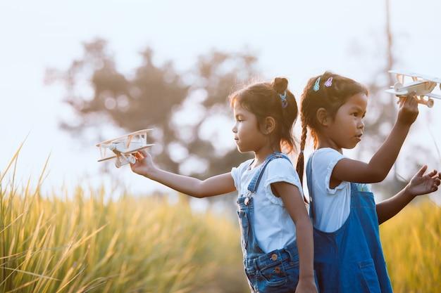 Duas meninas de criança asiática bonito brincando com o avião de brinquedo de madeira no campo
