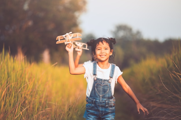 Duas meninas de criança asiática bonito correndo e brincando com o avião de brinquedo de madeira no campo