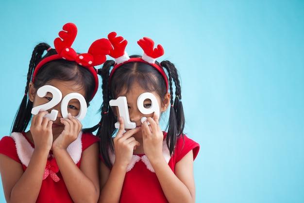 Duas meninas de criança asiática bonito segurando números 2019 para celebrar o feriado de ano novo