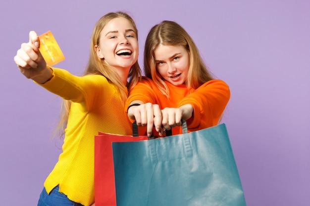 Duas meninas de irmãs gêmeas loiras felizes em roupas vivas, segurando o cartão do banco de crédito, sacola de pacote com compras depois de fazer compras isoladas na parede azul violeta. conceito de família de pessoas.