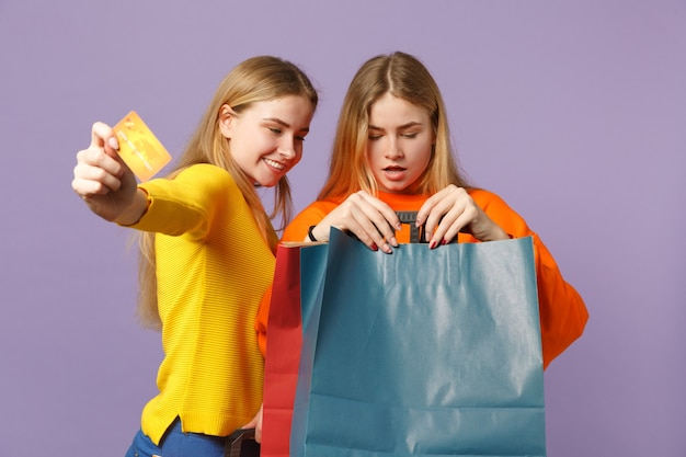 Duas meninas de irmãs gêmeas loiras sorridentes com roupas vivas segurar o cartão do banco de crédito, saco de pacote com compras depois de fazer compras isoladas na parede azul violeta. conceito de família de pessoas.