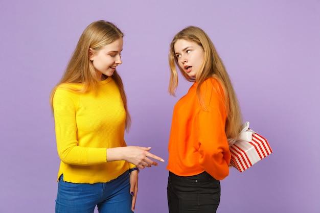 Duas meninas de irmãs gêmeas muito louras com roupas vivas, segurando uma caixa de presente listrada vermelha com fita de presente isolada na parede azul violeta. aniversário de família de pessoas, conceito de férias.