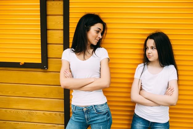 Duas meninas de pé segurando os braços cruzados