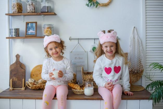 Duas meninas de pijama na cozinha depois de dormir bebem leite em casa