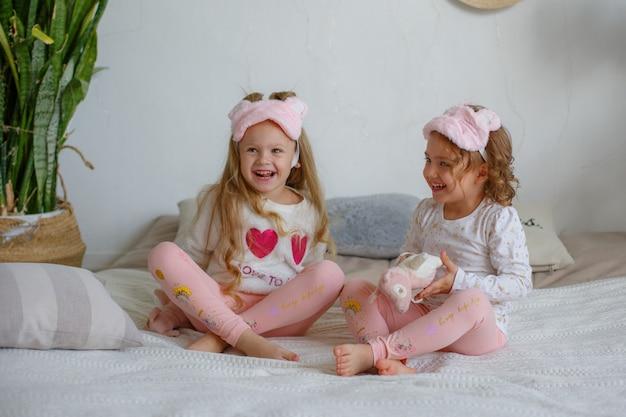 Duas meninas de pijama sentam na cama e se deliciam