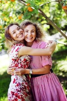 Duas meninas de sorriso bonitas abraçaram no parque do verão.