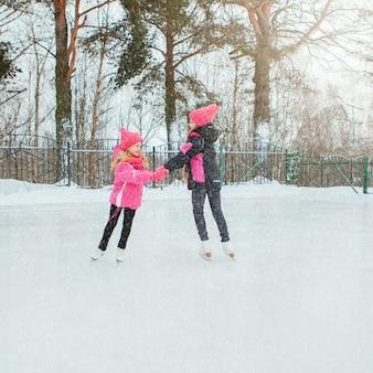 Duas meninas de sorriso pequenas que patinam no gelo no desgaste cor-de-rosa e em lenços feitos à mão.