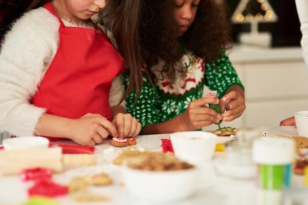 Duas meninas decorando biscoitos de natal