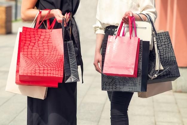 Duas meninas depois de fazer compras com sacos nas mãos.