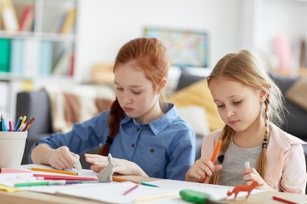 Duas meninas desenhando em casa