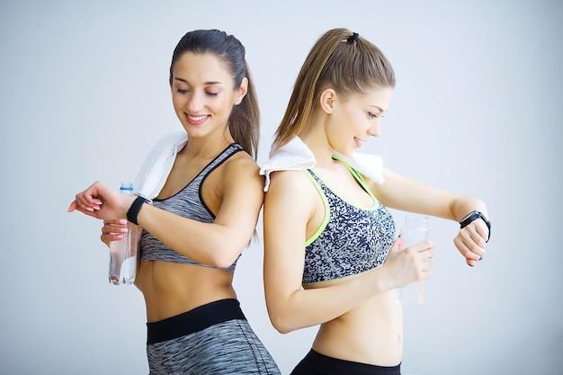 Duas meninas desportivas que olham algo no relógio esperto no gym.