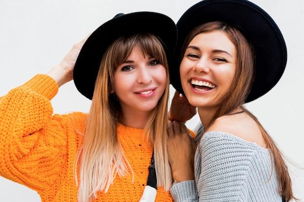 Duas meninas despreocupadas enviando beijo de ar em pé no branco