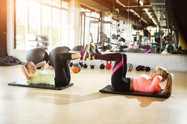 Duas meninas determinadas fazendo flexões com as pernas no ar.