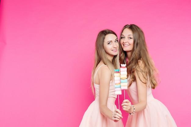 Duas meninas doces gostam de bonecas posando de rosa com marshmallow.