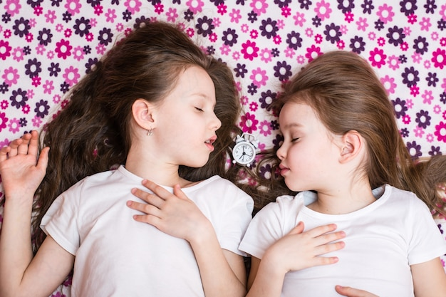 Duas meninas dormindo e um despertador branco no meio. vista do topo