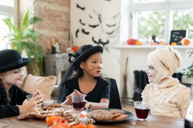 Duas meninas e um menino em fantasias de halloween tomando drinks com biscoitos
