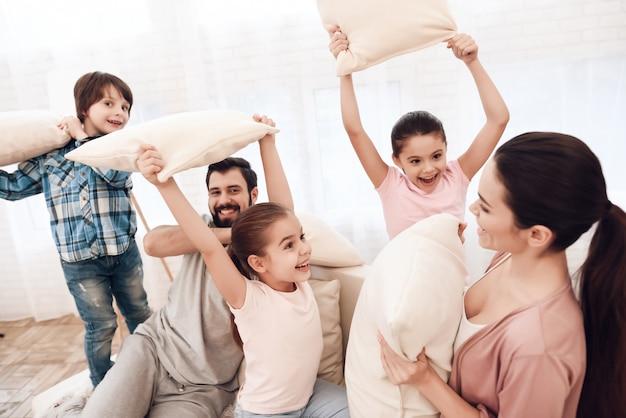 Duas meninas e um menino lutam com almofadas com seus pais.