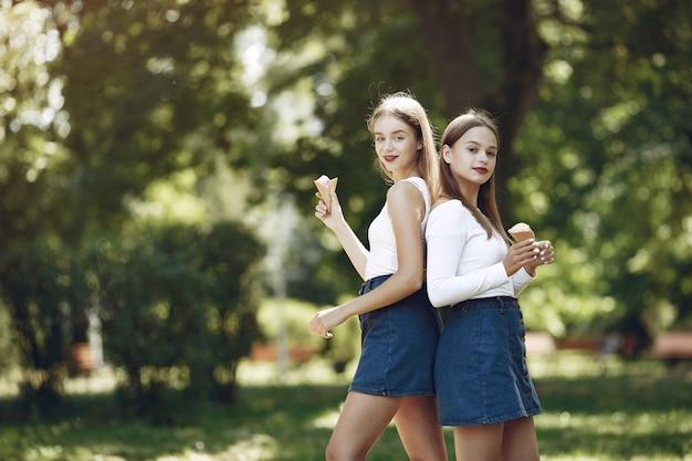 Duas meninas elegantes e com estilo em um parque primavera