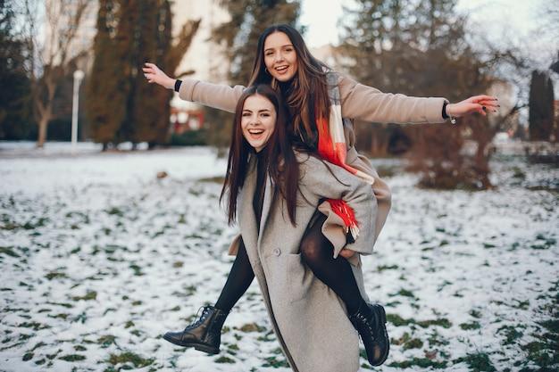 Duas meninas elegantes têm um descanso em uma cidade